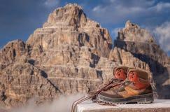 Wycieczkować buty na drewnianej ławce na pięknych górach krajobraz lub sceneria obraz stock