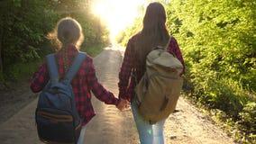 Wycieczkowicz dziewczyna dziewczyny podróż z plecakami na wiejskiej drodze kobieta turyści iść zmierzch Szcz??liwa rodzina na wak zbiory