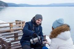 Wycieczkowicz pary obsiadanie przy pić herbatą i jeziorem obrazy royalty free