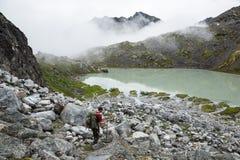 Wycieczkowicz pochodzi w kierunku zielonego glacjalnego jeziora w Hatcher przepustki terenie Obrazy Royalty Free