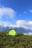 Wycieczkowicz _ s namiot na the wysoka góra, z śnieżny góra w the tło obraz royalty free