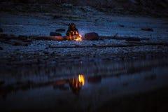 Wycieczkowicz siedzi blisko campingu ogienia przy rzecznym brzeg Pojęcie samotność, wybór, cisza obrazy royalty free