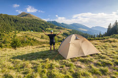 Wycieczkowicz stoi blisko turystycznego namiotu w górach Obrazy Royalty Free