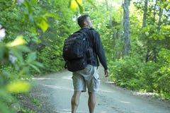 Wycieczkowicz zdumiewa się przy drzewami i przyrodą w lesie Obrazy Stock