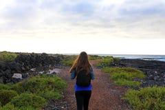 Wycieczkowicza żeński odprowadzenie w Lanzarote Tylny widok młodej kobiety hiki obrazy stock