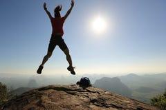 Wycieczkowicza doskakiwanie na wschód słońca góry wierzchołku Fotografia Stock