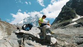 Wycieczkowicza mężczyzna freelancer daleko turystyczny działanie na naturze i używać komputerze w górach siedzi na kamieniu zdjęcia stock
