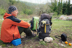 Wycieczkowicza obsiadanie i odpoczywać blisko dwa plecaków z kwiatami Zdjęcie Stock