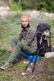 Wycieczkowicza obsiadanie i odpoczywać blisko dwa plecaków z kwiatami Fotografia Royalty Free