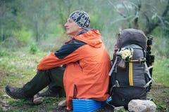 Wycieczkowicza obsiadanie i odpoczywać blisko dwa plecaków z kwiatami Zdjęcia Royalty Free