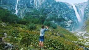 Wycieczkowicza podróżnik bierze wizerunek panorama smartphone - siklawa i góry Technologia w dzikiej naturze - obraz stock