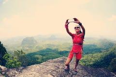 Wycieczkowicza use smartphone bierze jaźni fotografię na nadmorski góry wierzchołku Obraz Royalty Free