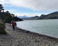 Wycieczkowicze na skalistym jeziorze wyrzucać na brzeg na W wędrówce w Torres Del Paine NP w Patagonia, Chile fotografia stock
