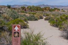 Wycieczkujący ścieżkę podpisuje obok piaskowatego przejścia w pustyni Obrazy Stock
