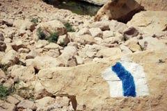 Wycieczkujący śladu markiera malował na kamieniu w skalistym pustynnym terenie Obrazy Stock