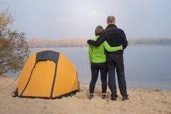 Wycieczkujący pary pozycję blisko namiotu w obozie na brzeg rzeki, Obraz Royalty Free
