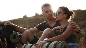 Wycieczkujący pary - wycieczkowicze odpoczywa na wzgórzu Młodej kobiety i mężczyzna wycieczkowicza obsiadanie na zmielony cieszy  zbiory wideo