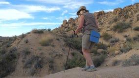 Wycieczkujący w Pustynnym Mojave, Dojrzała Aktywna kobieta Iść W dół wzgórza 4K zdjęcie wideo