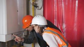 Wycofanie i czytania nacisk i temperatura w kotłowym pokoju żeński nadzorca i męski inżynier zdjęcie wideo