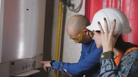 Wycofanie i czytania nacisk i temperatura w kotłowym pokoju żeński nadzorca i męski inżynier zbiory