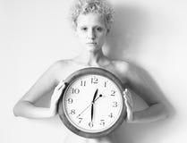 Wyczulona kędzierzawa dziewczyna z dużym zegarem w rękach Obraz Stock