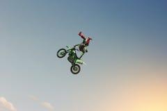 Wyczynu kaskaderskiego rowerzysta wykonuje sztuczkę w niebie Obrazy Royalty Free