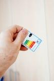 Wydajności energii etykietka w mężczyzna ręce Obraz Royalty Free