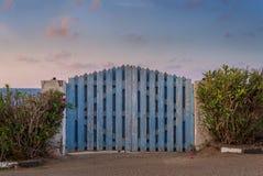 Wyginam się wietrzał błękitną drewnianą ogrodową bramę z zielonymi krzakami i częsciowo chmurnym niebem przy obimi stronami przy  Obrazy Stock