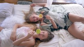 Wygodna atmosfera, siostry w jedwabniczych sleepwears je słodkich lizaki i opowiada lying on the beach na łóżku w domu zdjęcie wideo