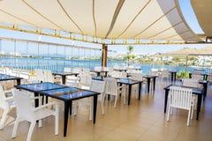 Wygodna grecka restauracja z biel krzesłami i błękitów stołami fotografia royalty free