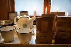 Wygodna porcji taca z ceramicznymi teacups, teapot, herbata i świeczki przed okno, - Brown papieru herbaciane torby z tekstem zdjęcia stock