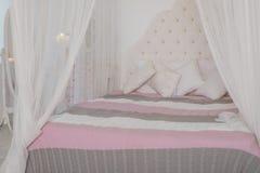 Wygodna sypialnia w lekkich pastelowych kolorach, wielki łoża łóżko z poduszkami Skandynawski prostota projekt Eco loft fotografia stock