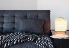 Wygodna szara kanapa, stołowa lampa i książka, Zdjęcia Royalty Free