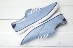 Wygodni przypadkowi buty na białym drewnianym tle zdjęcia stock
