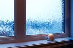 Wygodny świeczki palenie blisko frosted okno zdjęcie royalty free