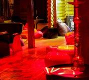 Wygodny atmosferyczny wnętrze kawiarnia w czerwonych brzmieniach Drewniany stół i krzesła pod miękką lampą zaświecamy Żadny gości zdjęcia stock