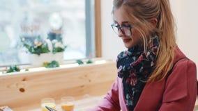 Wygodny café's wnętrze, ładna Europejska dziewczyna w, eleganckim przypadkowej odzieży obsiadaniu okno i używać jej kieszeniow zdjęcie wideo