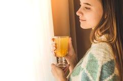 wygodny dom Kobieta z filiżanką gorący napój okno Patrzeć okno i napoju herbaty dzień dobry z herbatą Młodej dziewczyny relaksowa fotografia stock