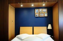Wygodny pokój z błękit ścianą, biel pokrywami i Drewnianą szafą, Zdjęcia Stock