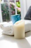 Wygodny spojrzenie, świeczka i kawowy kubek na bielu, fotografia stock