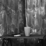 Wygodny workspace poj?cie Gor?cy nap?j i notatnik z bookmark na depresja stole blisko drewnianej ?ciany Fili?anka herbata lub kaw zdjęcie stock