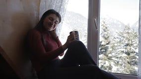 Wygodny zima styl życia Młoda szczęśliwa kobieta pije filiżankę kawy jest ubranym trykotowego puloweru obsiadania dom dużym okno zbiory wideo