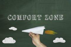 Wygody strefy pojęcie, Ludzka ręka trzyma papierowego samolot na chalkboard zdjęcie royalty free