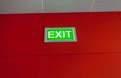 Wyjścia szyldowy jarzyć się na czerwieni ścianie Fotografia Stock