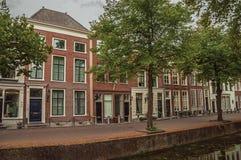 Wykładająca ulica z kanałem i fasadą eleganccy ceglani domy na chmurnym dniu w Delft Fotografia Stock