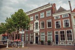 Wykładająca ulica z mostem, bicyklem i fasadą eleganccy ceglani domy w Delft, Fotografia Stock