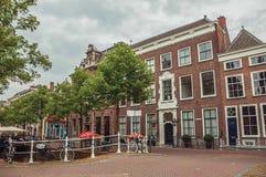 Wykładająca ulica z mostem, bicyklem i fasadą eleganccy ceglani domy w Delft, Obrazy Stock
