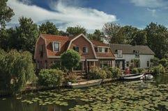 Wykładający kanał z nadwodnymi roślinami, łodziami na banku na słonecznym dniu w Weesp i cegła domem, Obraz Stock