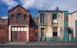 Wykolejenów domy i porzucająca handlowa własność na ulicie Obrazy Stock