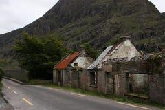 Wykolejenów domy w Irlandia wzdłuż głównej drogi z drzewami na tle Obrazy Stock